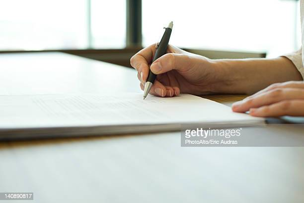 Person signing document, cropped