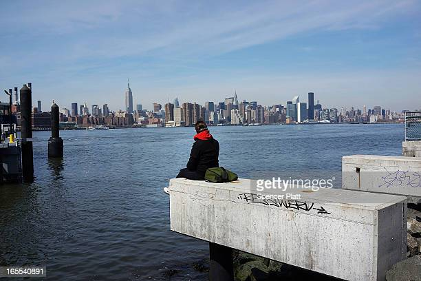 A person sits on the shore overlooking Manhattan while sitting along open space at the waterfront in the rapidly developing neighborhood of...