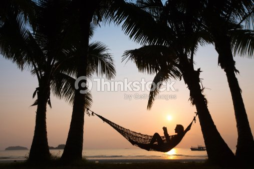 A person sitting in a hammock on the beach at sunset : Stock Photo