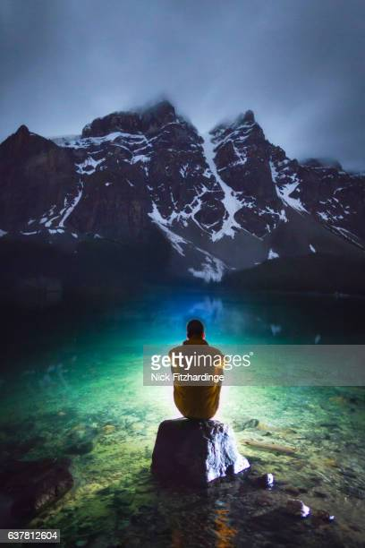 A person sitting on a rock out on the water of Moraine Lake at night, Banff National Park, Alberta, Canada