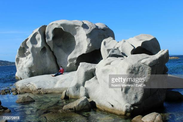 Person Sitting On Rock Formation In Sea Against Sky