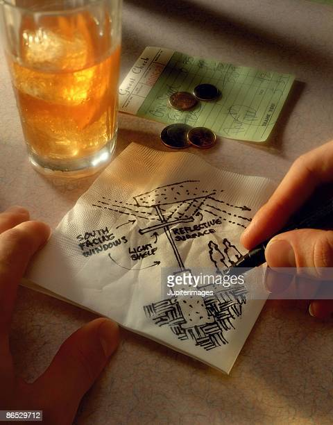 Person sketching on napkin in diner