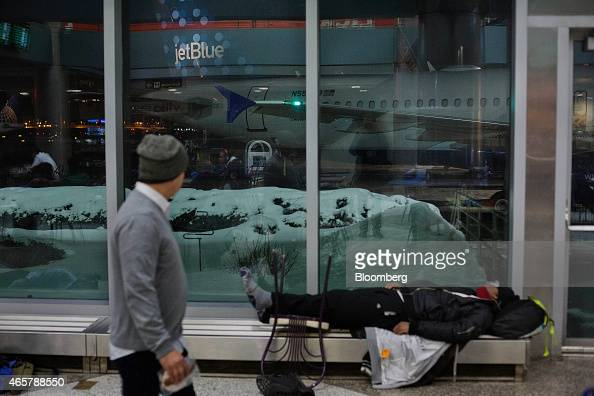 A person sleeps on a heater in Terminal B of LaGuardia Airport in New York on Saturday March 7 2015 While the homeless population is bigger at the...