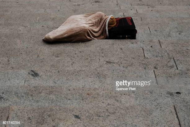 A person sleeps on the street in Manhattan on July 24 2017 in New York City In its annual homeless count New York City recorded 3892 people living on...