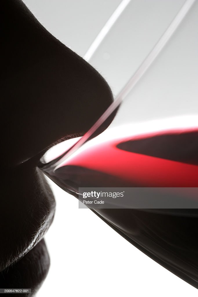 Person smelling glass of red wine : Stock Photo