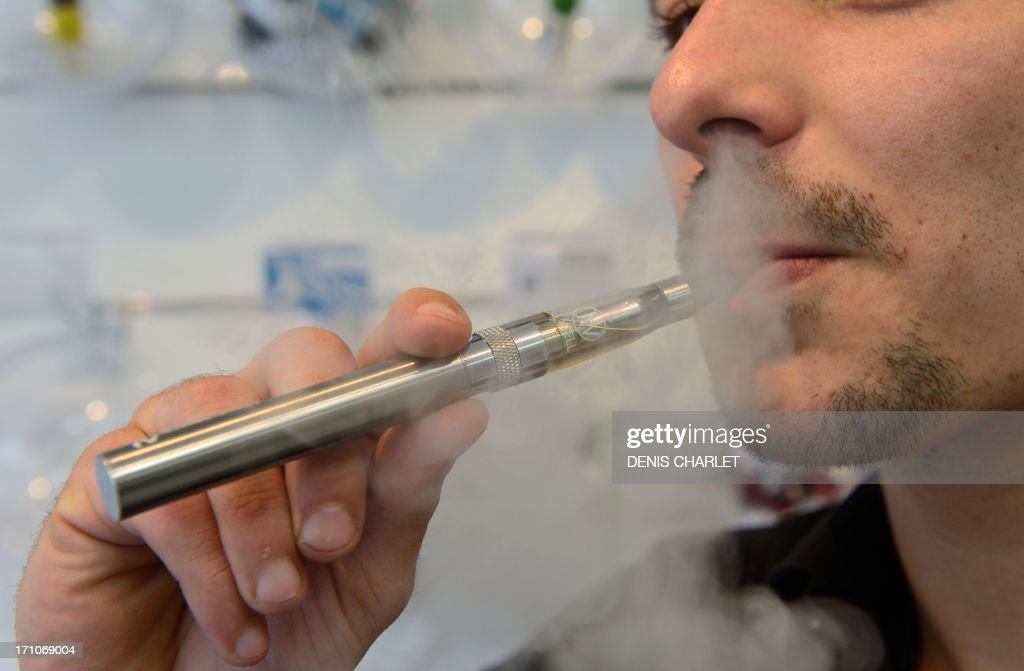 A person smokes an electronic cigarette in Lille on June 21, 2013. France said on May 31, 2013 that it would apply the same bans to electronic cigarettes as it does to tobacco but would not completely outlaw the popular smokeless product.