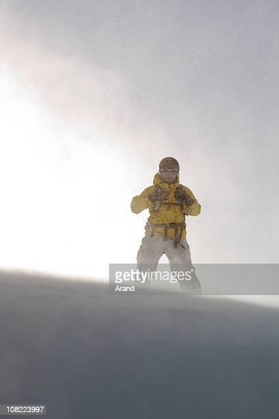 人スノーボードを山に吹く風と雪