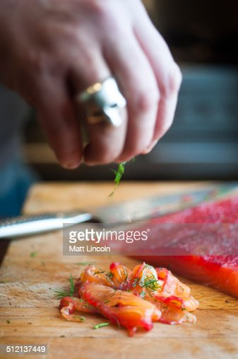 Person sprinkling dill on gravlax
