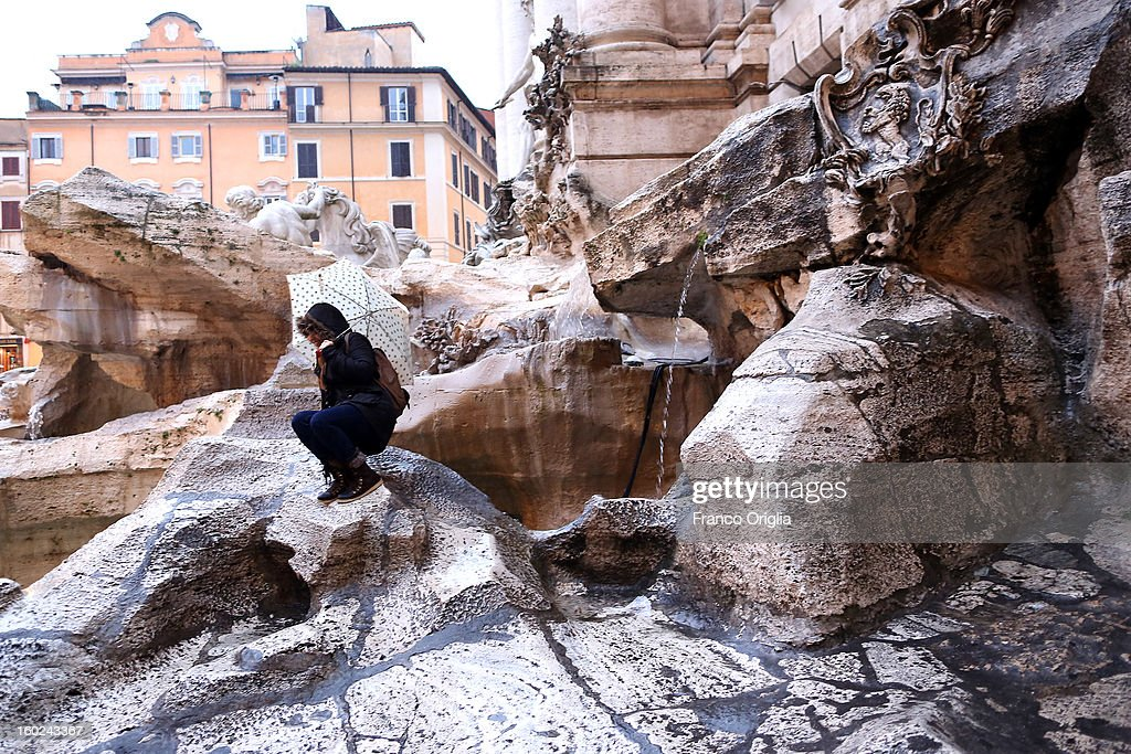 A person squats near the deteriorated marbles of Trevi Fountain on January 28, 2013 in Rome, Italy. FENDI Chairman and CEO Pietro Beccari together with Karl Lagerfeld and Silvia Venturini Fendi and the representatives of the City of Rome, including the Mayor Gianni Alemanno, today announced the sponsorship of the restoration of Rome's most iconic fountain.