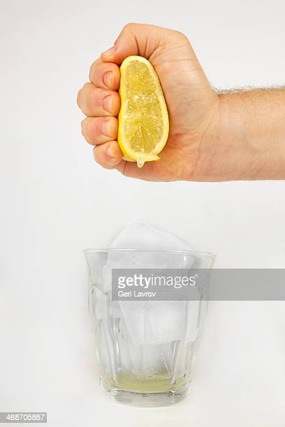 Person squeezing a lemon into a glass