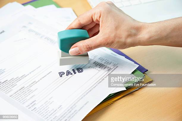 Person stamping paid on paperwork