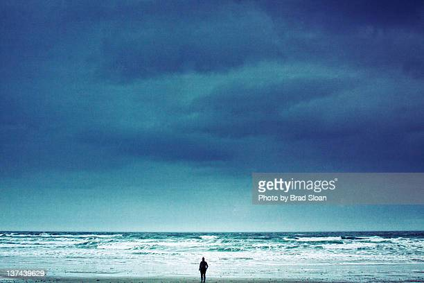 Person standing at edge of ocean
