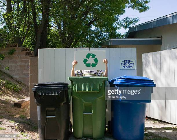 person standing behind waste bins holding recycling sign