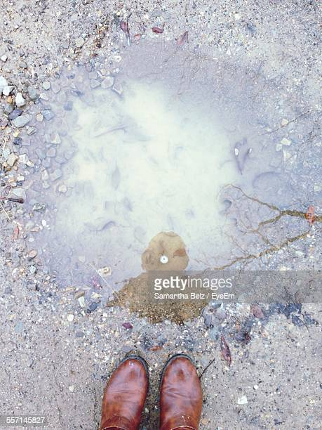 Person Standing By Puddle On Dirt