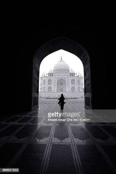 Person Standing In Arched Doorway Against Taj Mahal