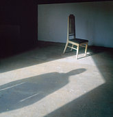 Person standing in doorway shadow on floor