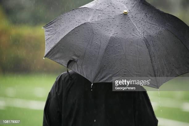 Person Standing in Rain with Black Umbrella