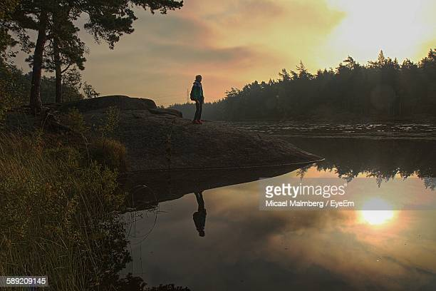 Person Standing On Rock By River Against Sky During Sunset