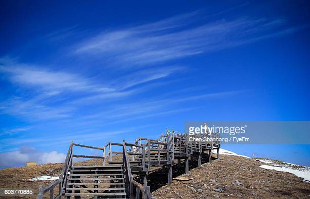 Person Standing On Steps At Mountain Against Sky