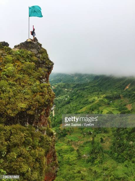 Person Standing On The Cliff Of Kandungaw Peak Against Sky