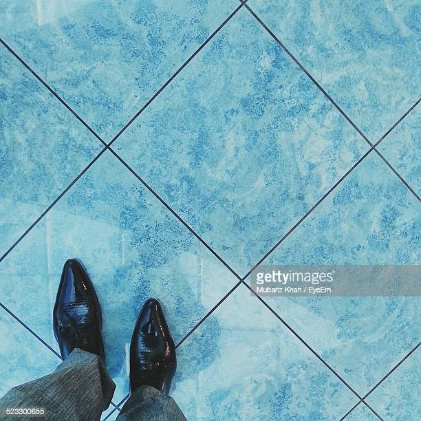 Person Standing On Tiled Floor