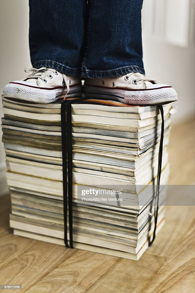 Person standing on top of bound stack of books and magazines