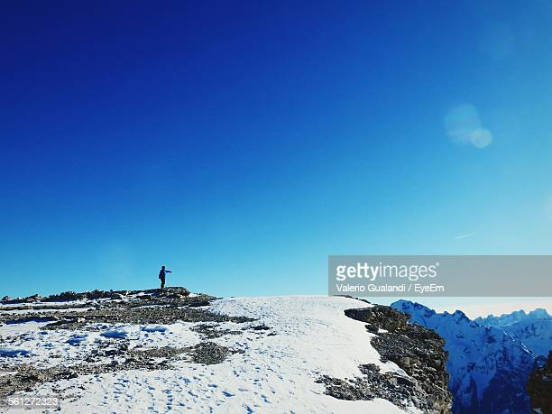 Person Standing On Top Of Mountain Against Blue Sky