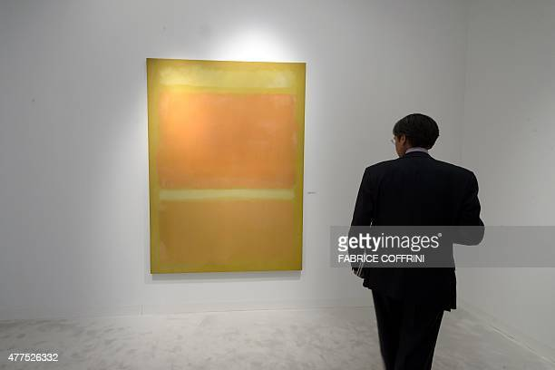 A person stands in front of an artwork by late US painter Mark Rothko entitled 'Untitled ' on June 17 2015 at the Helly Nahmad gallery during the...