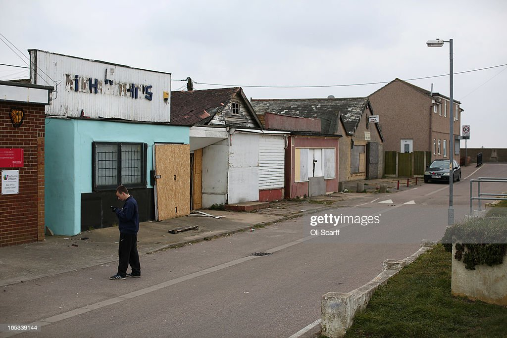 A person stands near dilapidated properties stand in the seaside town of East Jaywick, the most deprived place in England, on April 3, 2013 in Jaywick, England. The Government's 2011 Indices of Multiple Deprivation' measure ranks Jaywick as the most deprived of all 32,482 small wards in England and Wales. The area also has the greatest number of young people not in employment, education or training; one third of 16 to 24 year-olds claim Jobseeker's Allowance, compared to the national average of 6 per cent. Changes to the benefits and tax system which came into force on April 1, 2013 have included a cut in housing benefit payments for working-age social housing tenants whose property is deemed larger than they need and council tax support payments now being administered locally.