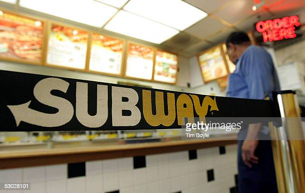 A person stands near signage while inside a Subway restaurant June 6 2005 in Chicago IllinoisSubway's Sub Club Customer Appreciation Card program is...