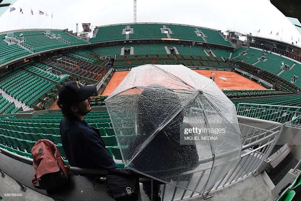 A person stands under an umbrella in the empty stands of the Philippe Chatrier court as play is suspended due to rain at the Roland Garros 2016 French Tennis Open in Paris on May 30, 2016. / AFP / MIGUEL