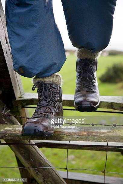 Person stepping over stile, outdoors, close-up, low section