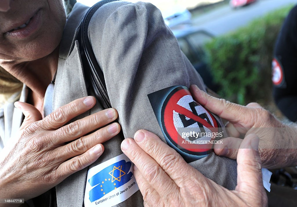 A person sticks a 'No Nazi' symbol in front of the Laszlo Csatary's last home building in Budapest on July 16, 2012, as she takes part in a demonstration called by the European Union of Jewish Students after a Hungarian prosecutors said that investigating an aged Nazi war criminal found alive and well in Budapest was problematic because the events took place so long ago and in a different country. A probe into Laszlo Csatary, 97, began in September after information was received from the Nazi-hunting Simon Wiesenthal Center, which ranks him number one on their wanted list, the public prosecutors' office said.