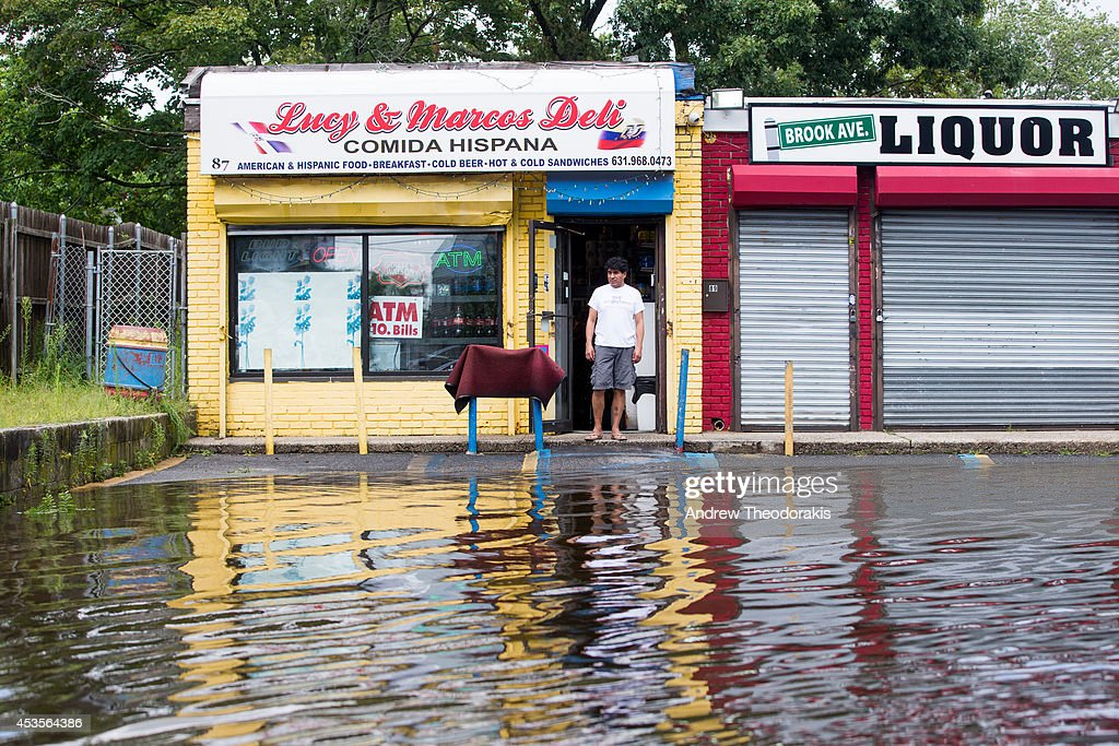 A person surveys flood water outside Lucy & Marcos Deli following heavy rains and flash flooding on August 13, 2014 in Bayshore, New York. The south shore of Long Island along with the tri-state region saw record setting rain that caused roads to flood entrapping some motorists.