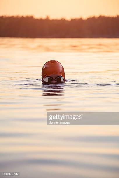 Person swimming at sunset