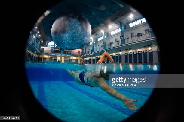 TOPSHOT A person swims under an artwork 'Museum of the Moon' by British artist Luke Jerram at the SaintGeorges swimming pool in Rennes western France...