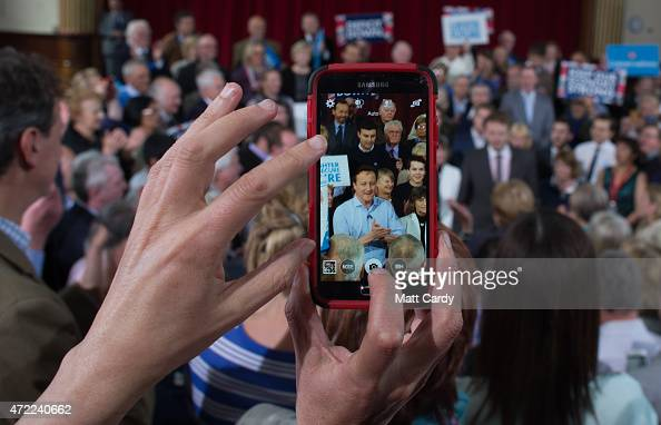 A person take a photo on their smartphone as Prime Minister David Cameron speaks to party supporters gathered inside the Guildhall in St Ives on May...