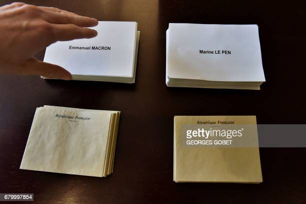 A person takes a ballot of French presidential election candidate for the En Marche movement Emmanuel Macron at a polling station in Tulle on May 7...