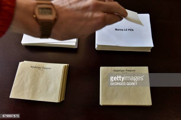 A person takes a ballot of French presidential election candidate for the farright Front National party Marine Le Pen at a polling station in Tulle...