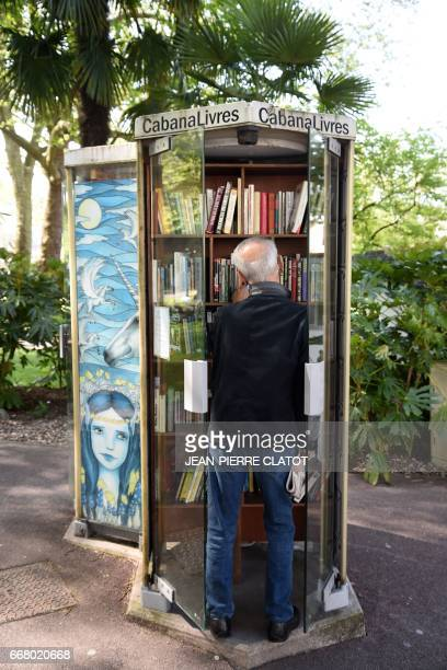 A person takes a book in a 'cabanalivres' on April 12 2017 in Aix les Bains Old telephone booths are converted into shelters for books / AFP PHOTO /...
