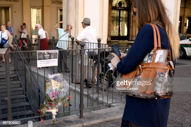 A person takes a photo of a sign and flowers in memory of Erika Pioletti who has died on June 16 from injuries sustained at the Champions League...