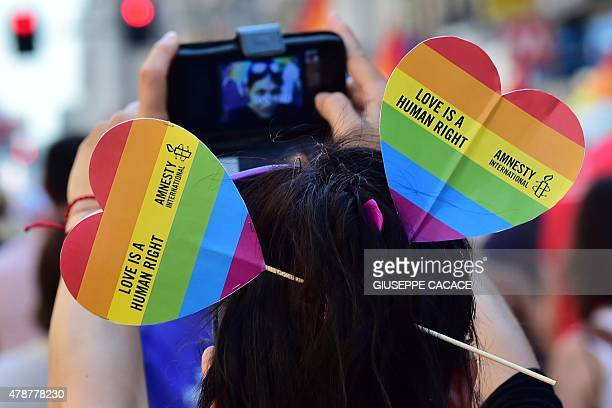 A person takes a picture during the annual Lesbian Gay Bisexual and Transgender Pride Parade in Milan on June 27 2015 AFP PHOTO / GIUSEPPE CACACE