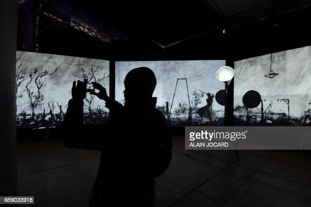 A person takes a picture of a piece of art by South African artist William Kentridge called 'more sweetly play the dance' as part of the exhibition...