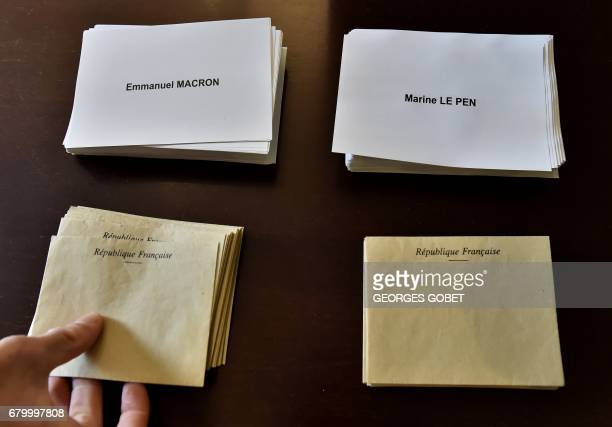A person takes an envelope at a polling station in Tulle on May 7 during the second round of the French presidential election / AFP PHOTO / GEORGES...
