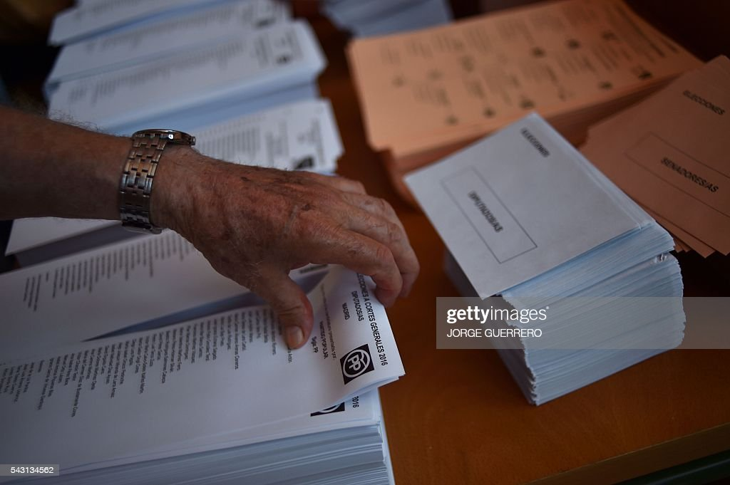 A person takes ballot sheets to vote in Spains general election at a polling station in cental Madrid on June 26, 2016. Spain votes today, six months after an inconclusive election which saw parties unable to agree on a coalition government. GUERRERO
