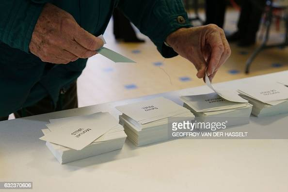 TOPSHOT A person takes ballots to vote at a polling station during the first round of the leftwing primary for the 2017 French presidential election...