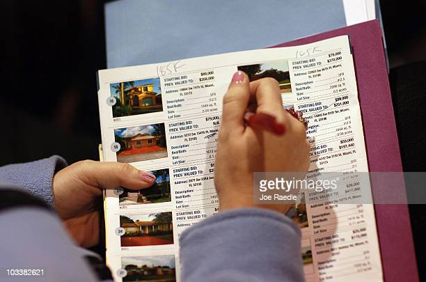 A person takes notes on the pamphlet listing the homes that are being auctioned off by Fannie Mae during the foreclosed home auction at the Miami...