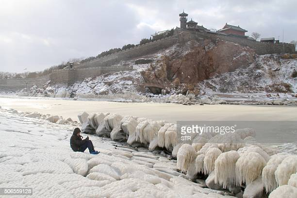 TOPSHOT A person takes photos of ice on the rocks by the seaside in Penglai in eastern China's Shandong province on January 24 2016 Much of China...