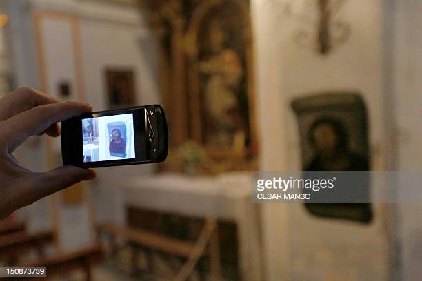 A person takes pictures of the deteriorated version of 'Ecce Homo' by 19thcentury painter Elias Garcia Martinez at the Borja Church in Zaragoza on...