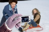 Person taking a picture of a heterosexual couple in the snow with a mobile phone, selective focus
